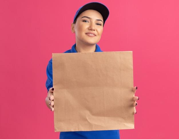Счастливая молодая женщина-доставщик в синей форме и кепке, держащая бумажный пакет, глядя вперед, весело улыбаясь, стоя над розовой стеной