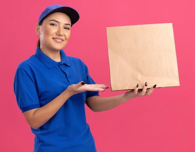 파란색 제복을 입은 행복 한 젊은 배달 여자와 분홍색 벽 위에 유쾌하게 서있는 웃는 앞을보고 팔을 제시하는 종이 패키지를 들고 모자