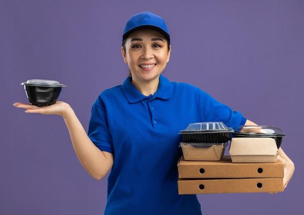 파란색 유니폼과 모자를 들고 피자 상자와 보라색 벽 위에 유쾌하게 서있는 음식 패키지를 들고 행복 젊은 배달 여자