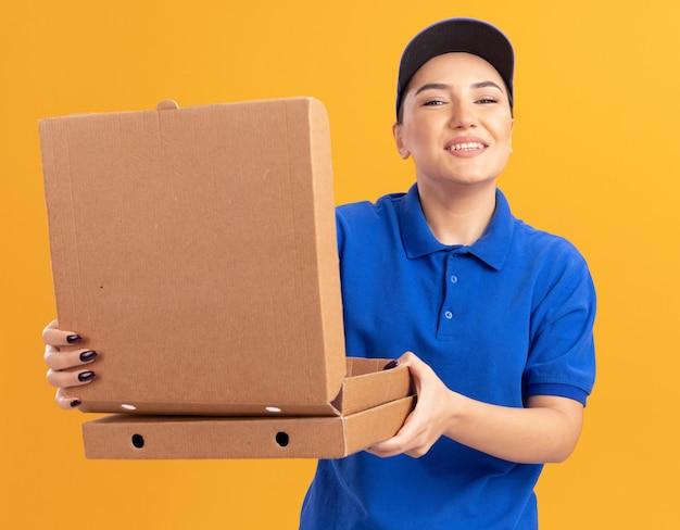 행복 한 젊은 배달 여자 파란색 유니폼과 모자를 들고 피자 상자 열기 상자 앞에 오렌지 벽 위에 유쾌하게 서 웃 고보고