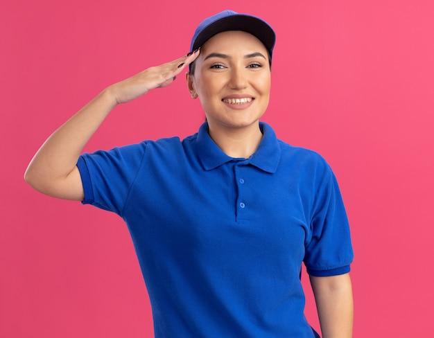 Счастливая молодая женщина-доставщик в синей форме и кепке, смотрящая вперед, улыбается, уверенно салютует, стоя над розовой стеной