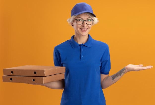 Счастливая молодая женщина-доставщик в синей форме и кепке в очках держит коробки для пиццы, весело улыбаясь над оранжевой стеной