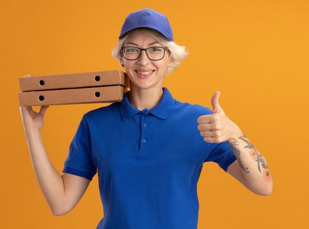 Счастливая молодая женщина-доставщик в синей форме и кепке в очках держит коробки для пиццы, улыбаясь, показывая большие пальцы руки над оранжевой стеной