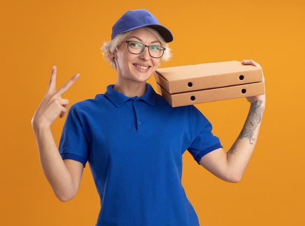 Счастливая молодая женщина-доставщик в синей форме и кепке в очках держит коробки для пиццы, улыбаясь, показывая v-знак над оранжевой стеной