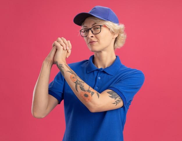 행복 한 젊은 배달 여자 파란색 유니폼과 모자 핑크 벽에 팀워크 제스처를 만드는 자신감이 식으로 모자