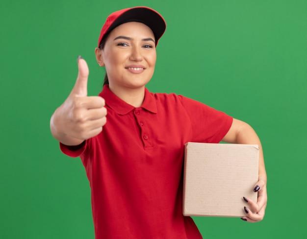 Счастливая молодая женщина-доставщик в красной форме и кепке держит картонную коробку, глядя вперед, весело улыбаясь, показывая большие пальцы руки вверх, стоя над зеленой стеной