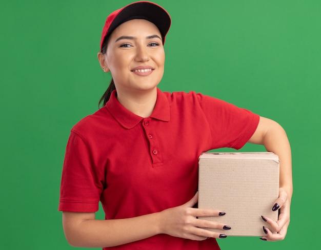 행복 한 젊은 배달 여자 빨간색 유니폼과 모자 녹색 벽 위에 유쾌 하 게 서 웃 고 앞을보고 골 판지 상자를 들고