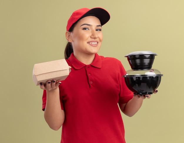 緑の壁の上に立っている顔に笑顔で正面を見て食品パッケージを保持している赤い制服と帽子の幸せな若い配達の女性