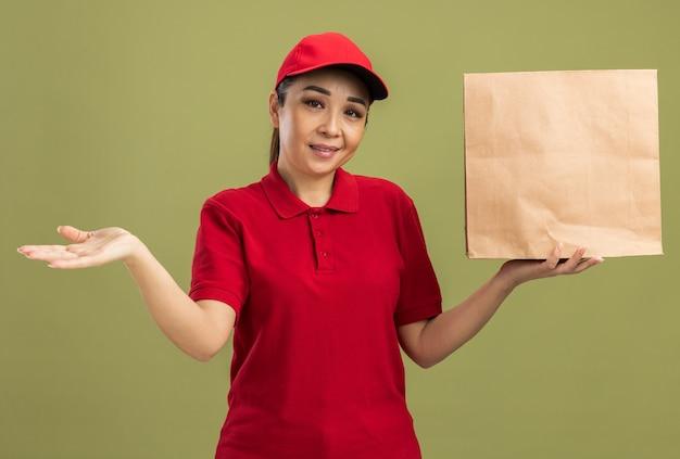 녹색 벽 위에 서있는 팔을 제시하는 얼굴에 미소로 종이 패키지를 들고 빨간 유니폼과 모자에 행복 젊은 배달 여자