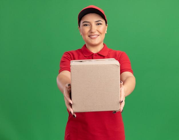 緑の壁の上に元気に立って笑顔の正面を見て段ボール箱を示す赤い制服とキャップの幸せな若い配達の女性