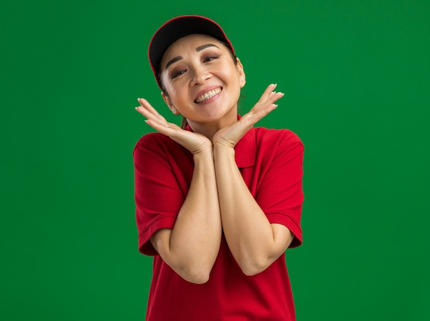행복 한 젊은 배달 여자 빨간 유니폼과 모자 녹색 벽 위에 서있는 얼굴 근처 손으로 친절 미소