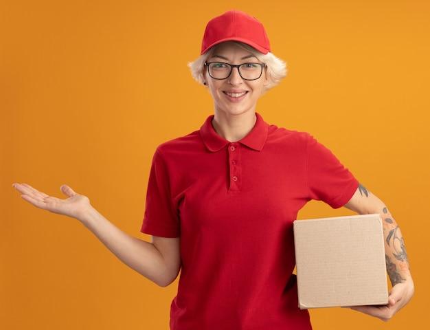 행복 한 젊은 배달 여자 빨간색 유니폼과 모자 오렌지 벽 위에 서있는 그녀의 손의 팔으로 복사 공간을 제시 미소 골 판지 상자를 들고 안경을 쓰고