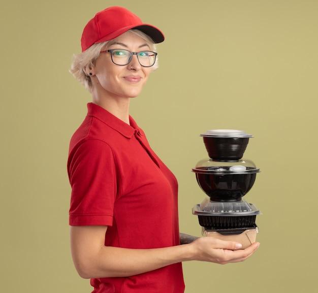 Счастливая молодая женщина-доставщик в красной форме и кепке в очках держит стопку продуктовых пакетов, уверенно улыбаясь, стоя над зеленой стеной