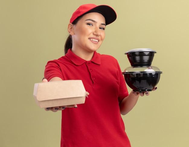 Felice giovane donna delle consegne in uniforme rossa e cappuccio che tiene i pacchetti di cibo guardando la parte anteriore con il sorriso sul viso in piedi sopra la parete verde