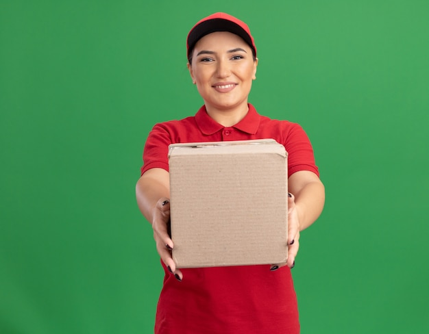 Happy young delivery woman in red uniform and cap showing cardboard box looking at front smiling cheerfully standing over green wall