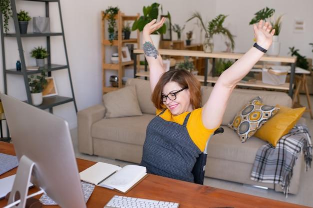 집에서 온라인 수업 후 컴퓨터 앞에 휠체어에 앉아있는 동안 그녀의 팔을 스트레칭 행복 젊은 비활성화 여성 학생