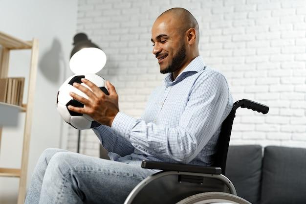 Счастливый молодой человек-инвалид в инвалидной коляске, держа футбольный мяч и улыбаясь