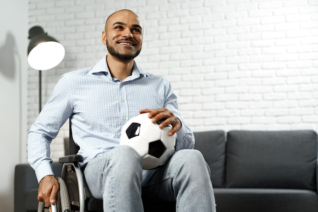 Happy young disabled man in wheelchair holding soccer ball and smiling