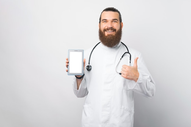 Happy young doctor man with beard showing tablet blank screen and showing thumb up over white wall