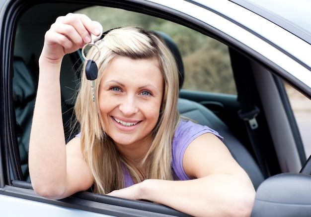 Счастливый молодой водитель, держащий ключ после того, как новый автомобиль
