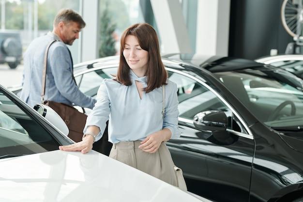 彼女の夫の白い色の新しい高級車の前部に触れるスマートカジュアルウェアの幸せな若いエレガントなブルネットの女性