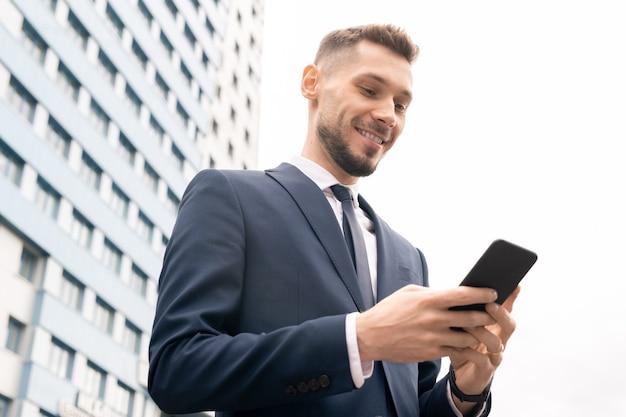 Счастливый молодой элегантный бизнесмен с прокруткой мобильного телефона в городской среде бизнес-центра