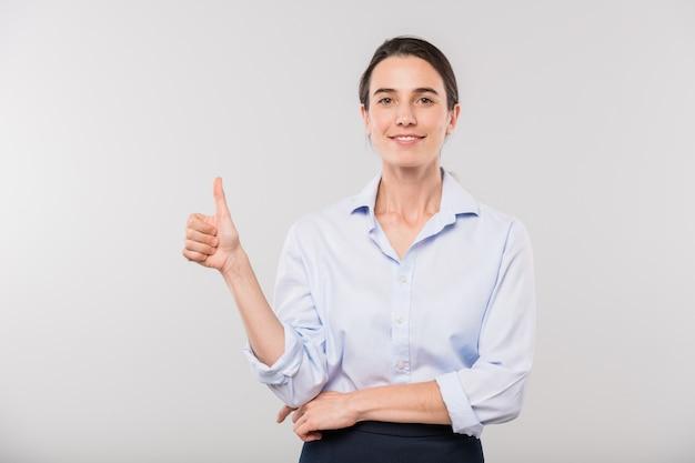 Счастливый молодой элегантный бизнесвумен в белой рубашке показывает палец вверх перед камерой в изоляции