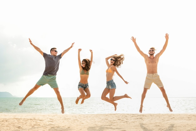 Happy young energetic group of friends jumping at the beach in summer