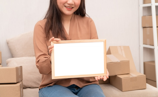 Happy young entrepreneur, sitting on the sofa and holding blank board for text and information.