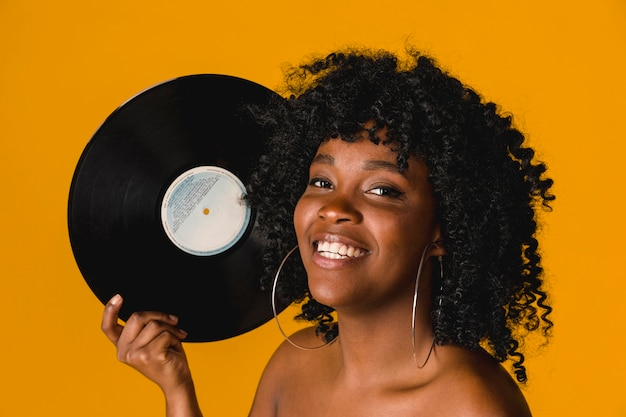Happy young ethnic woman holding vinyl plate on bright background