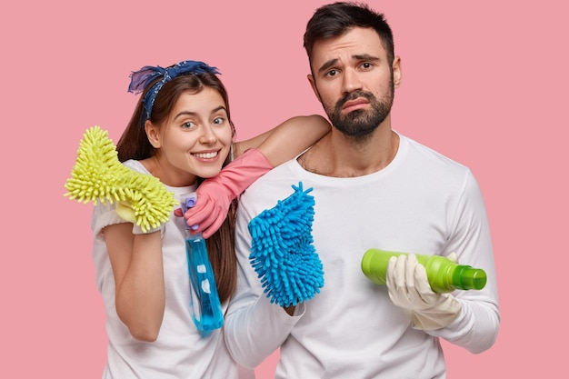 Happy young european woman and dissatisfied tired man hold detergents and rags, clean up room, dressed in white casual clothing, pose over pink wall. housekeeping and cleanliness concept