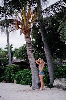 Счастливая молодая европейская женщина в джинсовых шортах с леопардовым верхом и классической белой шляпе на тропическом экзотическом пляже, улыбаясь, позирует, весело проводя время.
