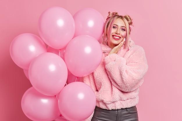 Счастливая молодая европейская женщина позирует с множеством воздушных шаров, наслаждается вечеринкой в свой день рождения, улыбается, с удовольствием носит шубу, есть еда, праздничное настроение ждет начала праздника