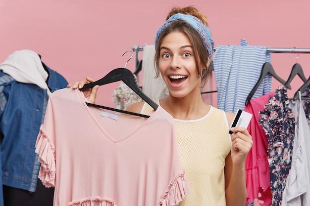 Счастливая молодая европейская шопоголика, чувствуя себя возбужденной, делая покупки в торговом центре города, и будучи удачной, чтобы сделать это до окончательной продажи, держит вешалку с модным топом и кредитной картой, собирается купить ее