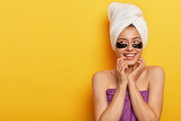 Happy young european woman touches skin gently, looks aside, applies beauty undereye patches, wrapped in towel, looks on left side