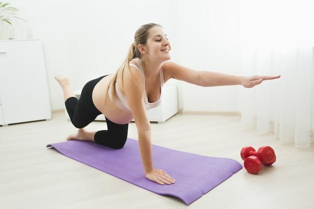 自宅でフィットネスマットの上で運動とストレッチをしている幸せな若い妊婦
