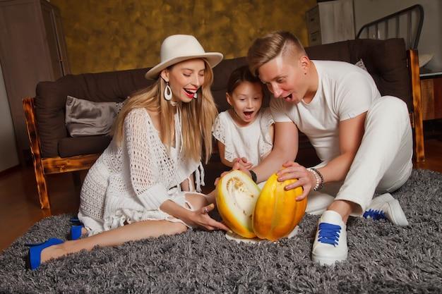 部屋のインテリアで家にいる幸せな若い家族は床にメロンを切りました。ママ、パパ、4歳の娘。家にいる人。母の、父の、子供の日の概念。サイトの著作権スペース