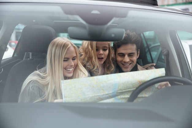 Happy young family in car holding map.