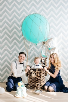 Happy young family celebrates the first birthday of the child. the baby is 1 year old. the concept of a children's party with balloons