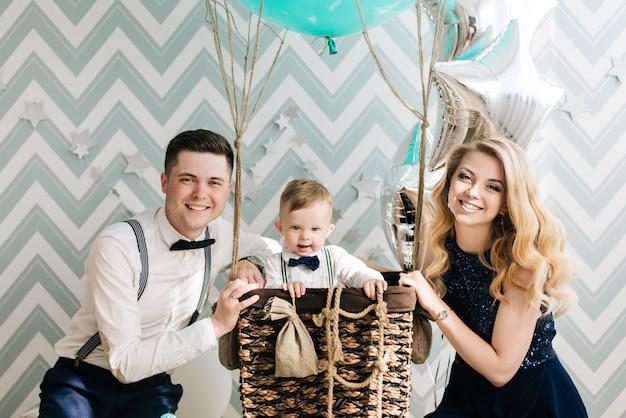 幸せな若い家族は子供の最初の誕生日を祝います。赤ちゃんは1歳です。風船で子供たちのパーティーのコンセプト