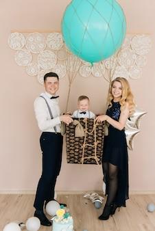 幸せな若い家族は子供の最初の誕生日を祝います