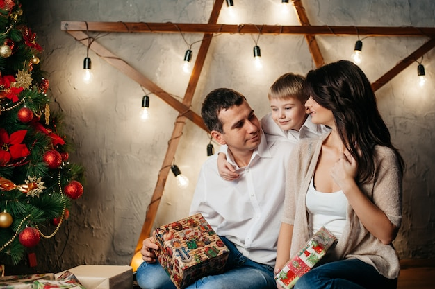 Happy young family in christmas decorations, mom, dad and little boy near christmas tree with presents near