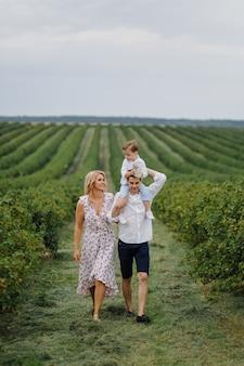 幸せな若い家族のお父さん、お母さん、幼い息子は公園で幸せそうに見える