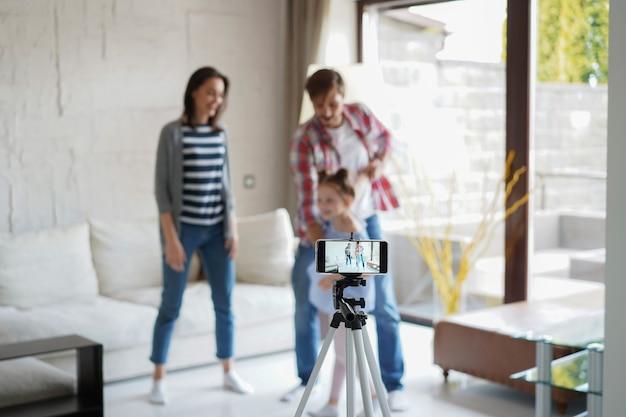 Счастливая молодая семья танцует дома со своей маленькой милой дочерью, снимая видео.