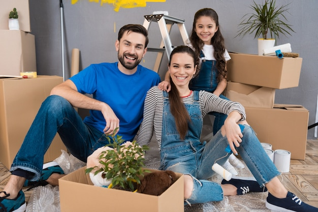 Happy young family dismantles cardboard boxes.