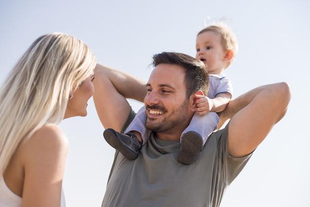 美しい晴れた日に一日を楽しんで幸せな若い家族