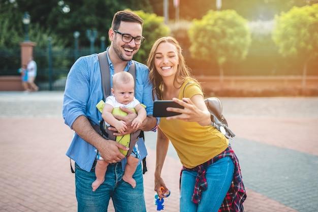 Счастливая молодая семья, наслаждаясь вместе и принимая фото selfie.