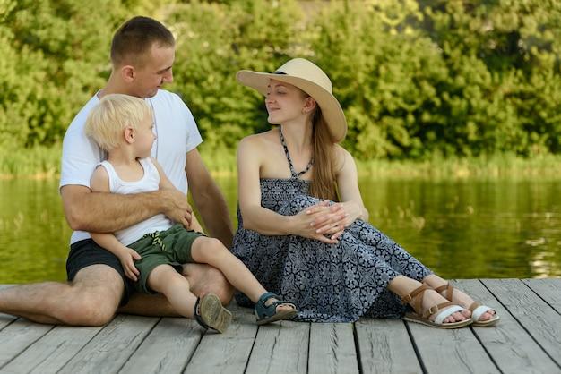 Счастливая молодая семья, отец-мать и маленький белокурый сын сидят на берегу реки.