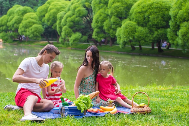 Happy young family of four picnicking near the lake