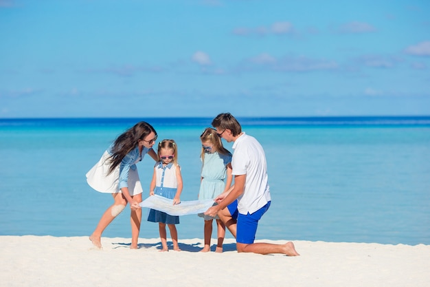 Happy young family of four with map on the beach